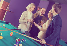 Adults with wine at billiard table. Group of joyful smiling different age friends with wine chatting near billiard table Royalty Free Stock Photos