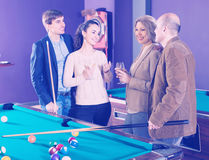 Adults with wine at billiard table. Group of smiling different age friends with wine chatting near billiard table Royalty Free Stock Images