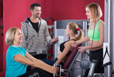 Adults working out in gym. Several smiling women and men having workout on machines in gym. Focus on woman Royalty Free Stock Photo