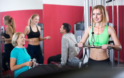 Adults working out in gym. Smiling women and men having powerlifting training on machines in fitness club Royalty Free Stock Images