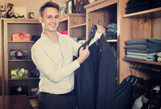 Adutl man is deciding on for new dark blue suit. In male clothes store Royalty Free Stock Image