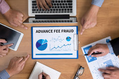 ADVANCE-FEE FRAUD. Business team hands at work with financial reports and a laptop, top view royalty free stock image