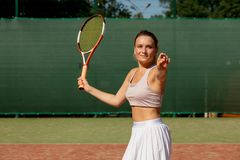 Advanced female player returns a ball during second set of International Cup. Tennis player female beginner playing with racket hitting ball with forehand on stock images