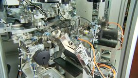 Advanced industrial production line for small parts, robotic arms working. Advanced industrial production line for small medical parts stock video footage