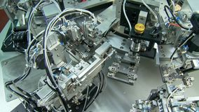 Advanced industrial production line for small parts, robotic arms working stock footage