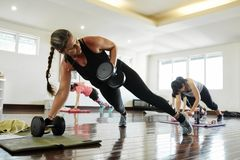 Advanced plank workout. Pretty Caucasian women doing plank exercise with heavy dumbbells royalty free stock images
