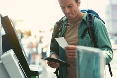 Joyful guy is waiting for flight. Advanced traveler. Cheerful man with backpack is standing nearby self-service check-in kiosk and holding tickets. He is Stock Photography