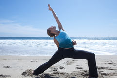 Advanced Yoga on Beach. Reaching back toward the sky in blue with a blue backround Stock Photos