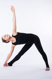 Advanced yoga posture, demonstrated by bloden girl, dressed in black, on white background.  royalty free stock images
