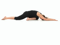 Advanced yoga practice variation. Young girl in yoga pose, side view, dressed in black, on white background Stock Photo