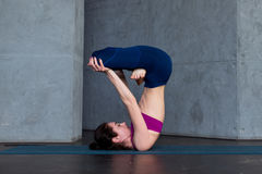 Advanced young yogini practicing Hatha yoga standing in inverted lotus pose, padmasana, on mat Royalty Free Stock Image