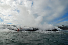 Advancing Lava, Ocean, Steam, Sky. Red hot lava flows into the ocean, bringing up clouds of steam and toxic gas, adding new land to the Big Island Stock Photography