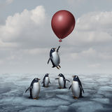 Advantage Business Concept. And leadership innovation metaphor as a group of penguins standing on ice with one individual rising up with a balloon as a royalty free illustration