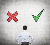 Advantages and disadvantages. Businessman looking at wall with advantages and disadvantages Stock Photo