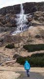 Advature man human scale with majestic waterfall mountain size. Stock Photos