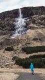 Advature man human scale with majestic waterfall mountain size. Royalty Free Stock Image
