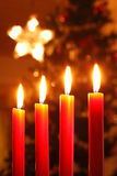 Advent. Candles with a star and a christmas tree in the background Stock Photos