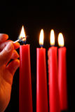 Advent. A womans hand lighting a advent candlestick Stock Photos