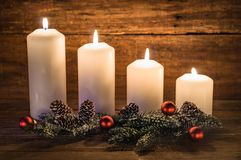 Advent. Candles with natural decoration of green fir branches, pine cones and red christmas balls. Four candles burning stock image
