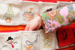 Advent Calendar. Little girl hand reaching into pocket of advent Christmas calendar Stock Photos