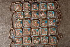 Advent calendar, Christmas handmade gingerbread painted icing. On a linen background Royalty Free Stock Photo