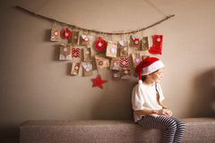 The advent calendar hanging on the wall. small gifts surprises for children. girl dressed as a dwarf royalty free stock image