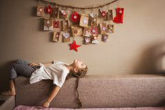 The advent calendar hanging on the wall. small gifts surprises for children. girl lies and looks at the calendar.  stock photography