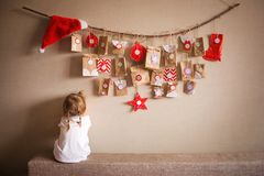 The advent calendar hanging on the wall. small gifts surprises for children. little girl playing peek-a-Boo stock image
