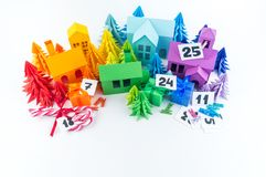Advent calendar for kids rainbow color. House and Christmas tree paper craft. Copy space. Advent calendar for baby rainbow color. House and Christmas tree paper stock photo