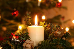 Advent Candle. Burning advent candle in front of a Christmas tree royalty free stock photo
