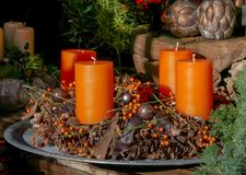Advent Candles Decoration mit Kiefern-Kegeln und Blätter, orange Farbe und hölzerne Elemente stockfoto