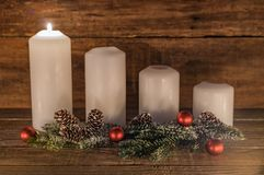 Advent. Candles with natural decoration of green fir branches, pine cones and red christmas balls. One candle is burning royalty free stock photography