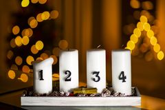 Advent candles in a row with decoration on a stand with christmas tree and a triangle candle on a background stock photography