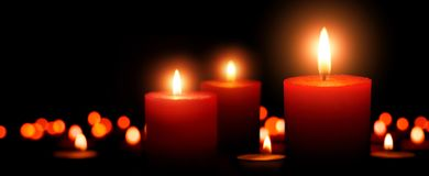 Advent candles, three flames in the foreground royalty free stock image