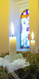 Advent candles on the wreath. Against stained-glass window Royalty Free Stock Photo