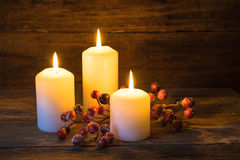 Christmas background with burning candles and red berries decoration. Royalty Free Stock Images
