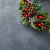 Advent christmas door wreath with festive decoration. Holidays new year concept. Advent christmas door wreath with festive decoration on a cozy black background royalty free stock photography