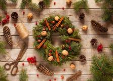Advent Christmas-Kranz mit natürlichen Dekorationen, Kiefernkegel putzen, Nüsse, kandierte Frucht auf hölzernem rustikalem Hinter Stockbild