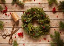 Advent Christmas-Kranz von Kiefernniederlassungen, -beeren und -kegeln auf alter Weinlesetabelle Stockbild