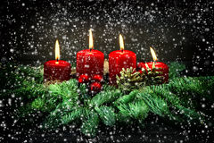 Advent Decoration Cuatro velas ardientes rojas con nieve que cae Fotografía de archivo