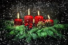 Advent Decoration Vier rote brennende Kerzen mit fallendem Schnee Stockfotografie