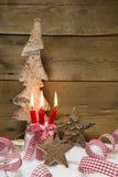 Advent: tre röda bränningstearinljus med julgarnering Royaltyfri Foto