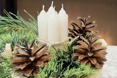 Advent. White wax candles tied with twine, pine branch and pine cones, green tinsel on the background of the fireplace. royalty free stock photo