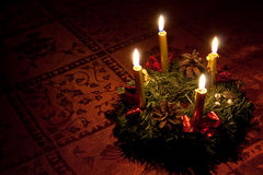 Advent wreath with candles. Advent wreath with burning candles on the red tablecloth Royalty Free Stock Image