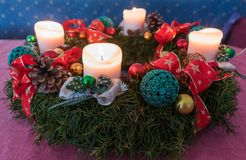 Advent wreath with four lighted white candles and red ribbons Stock Photo