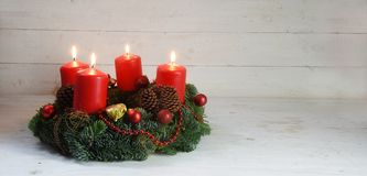 Advent wreath with four red burning candles and christmas decoration on rustic white wood, panorama format with copy space. Selected focus, narrow depth of stock image