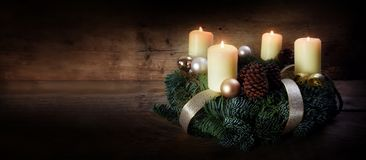 Advent wreath with four white burning candles and christmas decoration on rustic dark wood, panorama format with copy space. Selected focus, narrow depth of stock photo