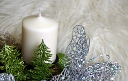 Advent wreath with white candle and glittery butterfly. And trees Stock Photography