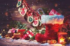 Adventkalender och sko för jultomten` s med gåvor på lantlig träbac Arkivfoto