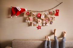 Adventkalendern som hänger på väggen små gåvor förvånar för barn arkivbild